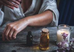 יד אישה מונחת על שולחן עץ בסמוך לנר דולק, בקבוק שמן ובקבוקון