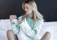 אישה יושבת על מיטה ובוחנת את בקבוקון סיבידי