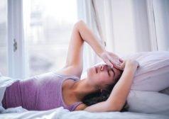 אישה שוכבת במיטה, מניחה את כף ידה על פניה