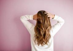 אישה אוחזת בראשה עם גבה מופנה