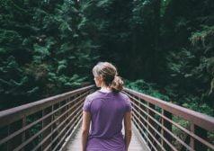 אישה חוצה גשר עץ בשמורת טבע