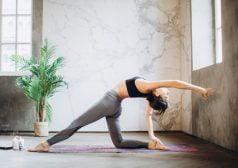 אישה מתמתחת בעת פעילות ספורטיבית בחדר עם קירות שיש ועציץ
