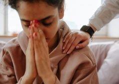 אישה אוחזת את שתי ידיה בסמוך לפניה בתנוחת תפילה