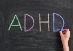 כף יד כותבת את המילה ADHD באנגלית בגירים ציבעוניים