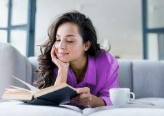 אשה קוראת ספר לצד ספל קפה
