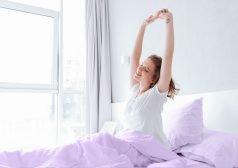 אשה קמה משינה עם חיוך ומתמתחת