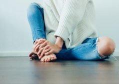 אישה הסובלת מכאב יושבת על הרצפה