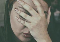 אישה אוחזת את ראשה בכף ידה