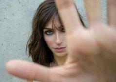 אישה מושיטה את האצבעות אל עבר העדשה