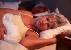 אישה שוכבת במיטה לצד בעלה הישן