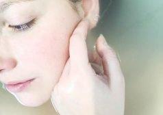 אישה מלטפת את עור הפנים