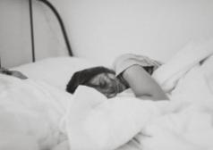אישה שוכבת במיטה מכורבלת בשמיכה