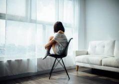 ילדה בדיכאון יושבת על כסא ליד החלון