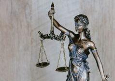 פסל מתכת של תמיס אלת הצדק אוחזת במשקל