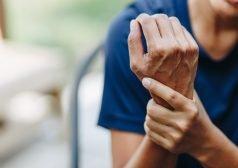 אישה צעירה אוחזת במפרק כף ידה