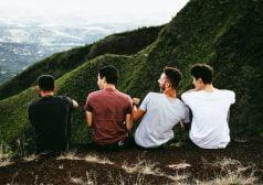 חבורת בני נוער יושבים על גבעה וצוחקים