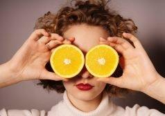 אישה אוחזת פרי הדר חצוי לפני עיניה