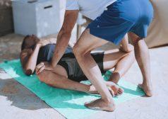מטופל שוכב על מזרון יוגה בעת טיפול על ידי מעסה מקצועי