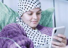 אישה מחוברת לעירוי שוכבת במיטה ומחזיקה טלפון נייד