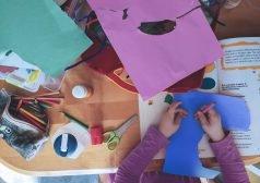 ילדה יושבת לצד שולחן יצירה עם עפרונות צעבעוניים, בריסטולים ומספריים