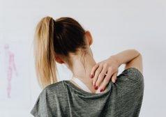 אישה אוחזת בעורפה בכאב